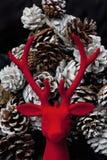 Renna decorativa di Natale sul pinecone rosso del fondo del velluto Fotografia Stock