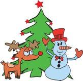 Renna e pupazzo di neve dietro l'albero di Natale Fotografie Stock