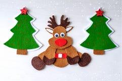 Renna fatta a mano di Rudolph di natale della cartolina d'auguri da feltro con l'albero di Natale, stelle rosse Fotografia Stock