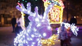 Renne allumé du ` s de Santa Claus contre l'arbre de Noël banque de vidéos