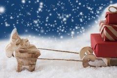 Renne avec le traîneau, flocons de neige bleus fond, l'espace de copie Photographie stock libre de droits