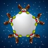 Renne di Natale che tengono palla di neve sopra fondo blu Immagine Stock