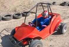 Rennen eines Jugendlichen auf einem Kind-` s Buggy entlang der Sandbahn Stockbild