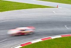 Rennenspur mit einem unscharfen Sportwagen Stockfotografie