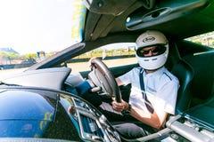 Rennwagen-Fahrer in einem Aston Martin Sports Car stockbild
