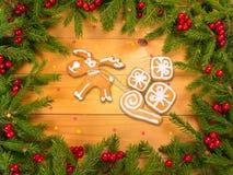 Reno con las galletas de los regalos en marco del árbol de navidad Foto de archivo