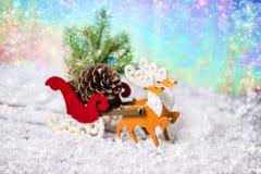Reno de la decoración de la Navidad y trineo de Papá Noel con el abeto t de la rama Imágenes de archivo libres de regalías
