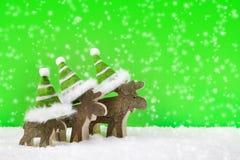 Reno de madera tres para la Navidad en un fondo verde con s Imágenes de archivo libres de regalías