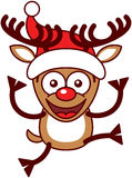 Reno de Navidad con las astas grandes, saltando y llevando un sombrero de Papá Noel ilustración del vector