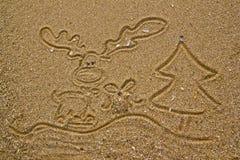 Reno, regalo y árbol de navidad drenados en la arena Imagen de archivo libre de regalías