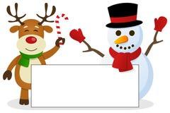 Reno y muñeco de nieve con la bandera en blanco Imagen de archivo libre de regalías