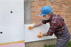 Renovación de la casa, aislamiento de la pared del poliestireno, colocación de la placa foto de archivo libre de regalías