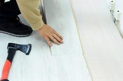 Renovación de un apartamento, hombre que pone el suelo laminado en el cuarto fotos de archivo libres de regalías