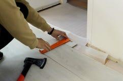 Renovación de un apartamento, hombre que pone el suelo laminado en el cuarto imagen de archivo libre de regalías