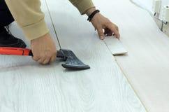 Renovación de un apartamento, hombre que pone el suelo laminado en el cuarto foto de archivo