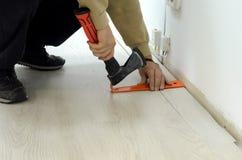 Renovación de un apartamento, hombre que pone el suelo laminado en el cuarto fotos de archivo