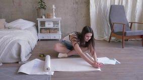 Renovación y diseño, muchacha hermosa en los guardapolvos de la mezclilla que preparan el rollo del papel pintado para marcar c almacen de video
