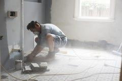 Renovador casero que usa las herramientas eléctricas que cortan en una pared Fotos de archivo
