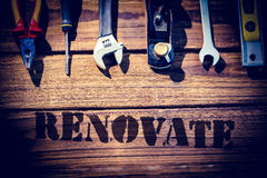 Renovate  against desk with tools. The word renovate  against desk with tools Stock Photo