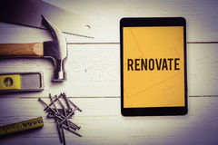 Renovate  against tablet displaying blueprint. The word renovate  and tablet pc against tablet displaying blueprint Stock Photos