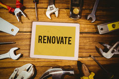 Renovate  against tablet on green background Royalty Free Stock Image