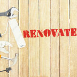 Renovate  against tools on wooden background Royalty Free Stock Photos