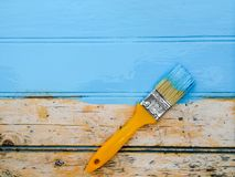 Renovate with a paint brush. Painting brush on a wooden board with blue paint Royalty Free Stock Image