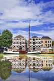 Renovated monumental mansion with white moored boat reflected in canal, Gouda, netherlands. Renovated monumental mansion with a white moored boat reflected in a Royalty Free Stock Images