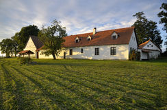 Renovated village homestead surrounded by grass field and trees Stock Photos