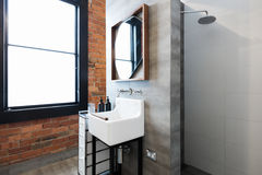 Renovated warehouse bathroom with vintage basin Stock Image