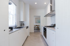 Renovated white galley style kitchen in modern apartment Royalty Free Stock Image