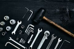 Renovating a car. A set of repair tools- hex keys, a hammer and a screwdriver on a black wooden background. Close up stock photography