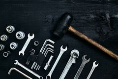 Renovating a car. A set of repair tools- hex keys, a hammer and a screwdriver on a black wooden background. Close up. Top view. Space for your text or product stock photo