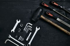 Renovating a car. A set of repair tools- hex keys, a hammer and a screwdriver on a black wooden background. Close up stock image