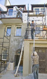 Renovating house facade. Three workers busy at a house facade, scaffolding structure and some materials and tools in a creative mess stock photos