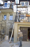 Renovating house facade. Three workers busy at a house facade, scaffolding structure and some materials and tools in a creative mess stock photo