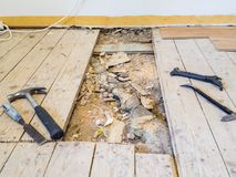 Renovating an old floor. Sawn a hole with tools lying around on the plank surrounding it Stock Photography