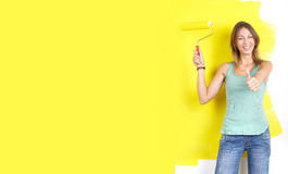 Renovation. Smiling beautiful woman painting interior wall of home Royalty Free Stock Photography