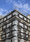 Renovation. Building Renovation with scaffolding in blue sky Stock Photo