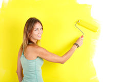Renovation. Smiling beautiful woman painting interior wall of home Stock Photos