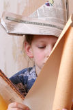 Renovation. Young girl with rolls of wallpaper Royalty Free Stock Images