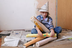 Renovation. Young girl sitting on a floor with rolls of wallpaper Stock Photos