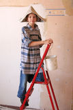 Renovation. Young girl on a ladder Royalty Free Stock Photo