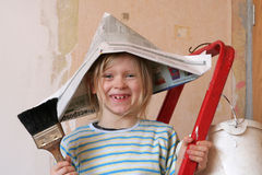Renovation. Little girl in newspaper hat on a ladder Stock Image