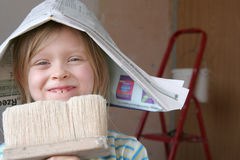 Renovation. Little girl in newspaper hat holding paintbrush Royalty Free Stock Photo