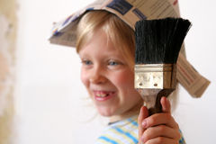 Renovation. Paintbrush against a background of a smiling girl Royalty Free Stock Image