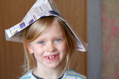 Renovation. Little girl in newspaper hat Royalty Free Stock Photography