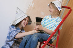 Renovation. Two girls quarreling about a paintbrush Royalty Free Stock Photo