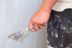 Renovation concept. Construction worker holding a trowel against unfinished drywall Stock Image