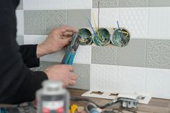 Renovation and construction in kitchen, close-up of electricians hand installing outlet on wall with ceramic tiles using. Professional tools royalty free stock photos